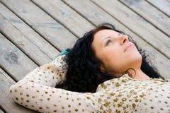 Mujer que miente en suelo de madera Fotografía de archivo