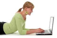 Mujer que miente en suelo usando la computadora portátil Imagenes de archivo