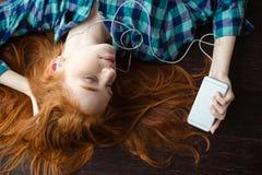 Mujer que miente en suelo y que escucha la música Fotografía de archivo