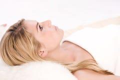 Mujer que miente en una cama cómoda del balneario Foto de archivo libre de regalías