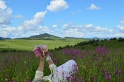 Mujer que miente en una escritura del campo de la primavera Fotos de archivo