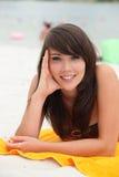 Mujer que miente en una toalla de playa Imagen de archivo libre de regalías