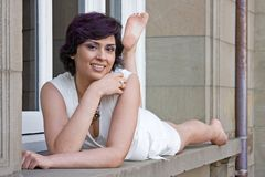 Mujer que miente en ventana Foto de archivo libre de regalías