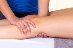 Mujer que miente mientras que consigue un concepto del masaje de la pierna de Imagenes de archivo