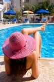Mujer que miente por una piscina grande el día de fiesta Foto de archivo libre de regalías