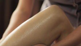 Mujer que miente y que tiene masaje de la pierna en el balneario metrajes