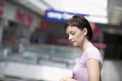 Mujer que mira abajo en centro comercial Foto de archivo