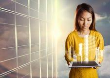 Mujer que mira abajo la tableta y el gráfico blanco del edificio contra ventana y el cielo de la tarde Fotografía de archivo libre de regalías