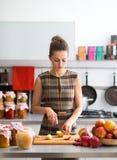 Mujer que mira abajo mientras que corta manzanas en cocina Imagen de archivo libre de regalías