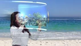 Mujer que mira actividades del día de fiesta en medios biblioteca interactiva en la playa almacen de video