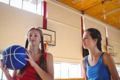 Mujer que mira al amigo que lleva a cabo baloncesto Fotos de archivo libres de regalías