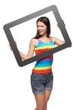 Mujer que mira al lado a través de marco de la tableta Imágenes de archivo libres de regalías