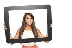 Mujer que mira al lado a través de marco de la tableta Fotos de archivo
