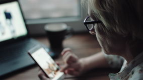 Mujer que mira algo en la pantalla del smartphone almacen de video