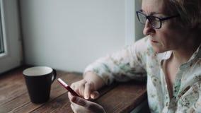 Mujer que mira algo en la pantalla del smartphone almacen de metraje de vídeo