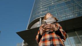Mujer que mira alrededor en el fondo de un rascacielos y que sostiene smartphone metrajes