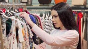Mujer que mira chocada por el precio de un vestido la tienda de ropa metrajes
