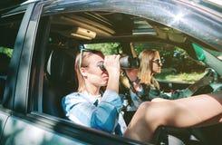 Mujer que mira con la conducción de los prismáticos y del amigo Foto de archivo libre de regalías