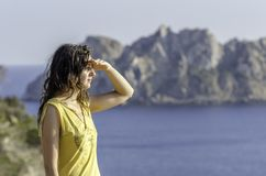 Mujer que mira con la mano en frente y el mar en el fondo Fotos de archivo