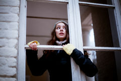 Mujer que mira con la ventana y el temor algo Imagen de archivo
