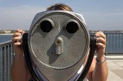 Mujer que mira con los prismáticos de fichas Imágenes de archivo libres de regalías