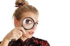 Mujer que mira con magnificar Foto de archivo libre de regalías