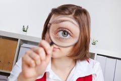 Mujer que mira con magnificar Imagen de archivo