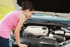 Mujer que mira debajo de Hood Car Imagen de archivo