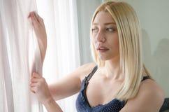 Mujer que mira detrás de la cortina Imagen de archivo libre de regalías