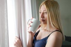 Mujer que mira detrás de la cortina Fotografía de archivo libre de regalías