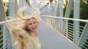 Mujer que mira detrás en el puente Mujer bastante rubia que mira detrás la cámara mientras que corre en el puente con el pelo ond metrajes