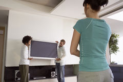Mujer que mira a dos hombres el mover de la televisión del plasma Fotos de archivo