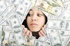 Mujer que mira el agujero del trought en bacground del dinero imágenes de archivo libres de regalías