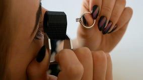 Mujer que mira el anillo a través de la lupa del joyero señora que intenta en un poco de joya en el boutique metrajes