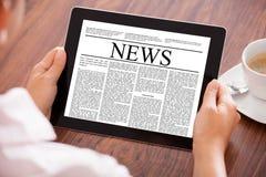 Mujer que mira el artículo de noticias Imágenes de archivo libres de regalías
