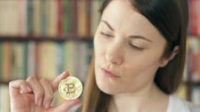 Mujer que mira el bitcoin del cryptocurrency Dinero virtual brillante del comercio en línea Foco en bitcoin almacen de metraje de vídeo