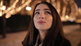 Mujer que mira el callejón maravilloso hermoso de la noche adornado por las guirnaldas amarillas de la luminosidad almacen de video