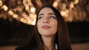 Mujer que mira el callejón maravilloso hermoso de la noche adornado por las guirnaldas amarillas de la luminosidad almacen de metraje de vídeo