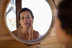 Mujer que mira el espejo en cabaña imagenes de archivo