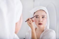 Mujer que mira el espejo y que usa la ceja del maquillaje del lápiz foto de archivo libre de regalías