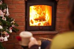 Mujer que mira el fuego en la chimenea Fotos de archivo libres de regalías