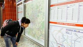 Mujer que mira el mapa del metro del subterráneo Imágenes de archivo libres de regalías