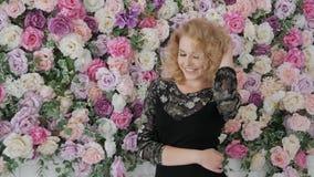 Mujer que mira el marco cerca de las flores metrajes