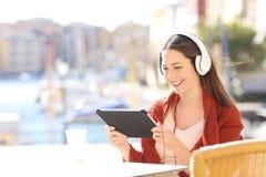 Mujer que mira el medios contenido en una tableta Fotos de archivo libres de regalías