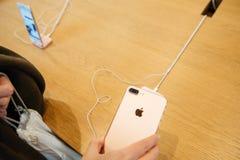 Mujer que mira el nuevo iphone doble 7 de la cámara Foto de archivo libre de regalías