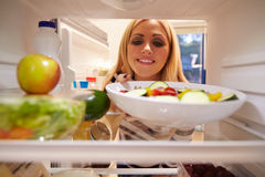 Mujer que mira el refrigerador interior por completo de la comida y que elige la ensalada Fotografía de archivo