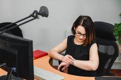 Mujer que mira el reloj mientras que se sienta en el ordenador Fotografía de archivo libre de regalías