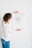 Mujer que mira el retrato del lápiz contra la pared foto de archivo