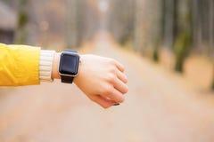 Mujer que mira el smartwatch mientras que teniendo un paseo Imágenes de archivo libres de regalías