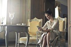 Mujer que mira el teléfono imágenes de archivo libres de regalías